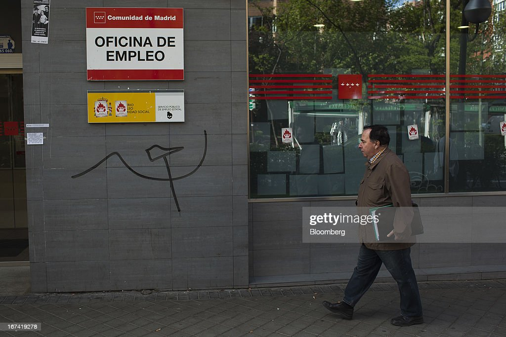 A pedestrian passes 'hammer and sickle' graffiti outside an employment office in Madrid, Spain, on Thursday, April 25, 2013. Spanish unemployment rose more than economists forecast in the first quarter to the highest in at least 37 years as efforts to tackle the European Union's biggest budget deficit crimped economic growth. Photographer: Angel Navarrete/Bloomberg via Getty Images