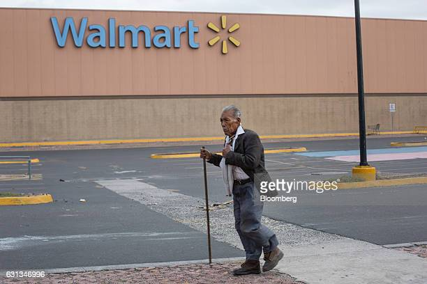 A pedestrian passes in front of a closed WalMart de Mexico SAB de CV after being looted during protests against the gasoline price hike in Veracruz...
