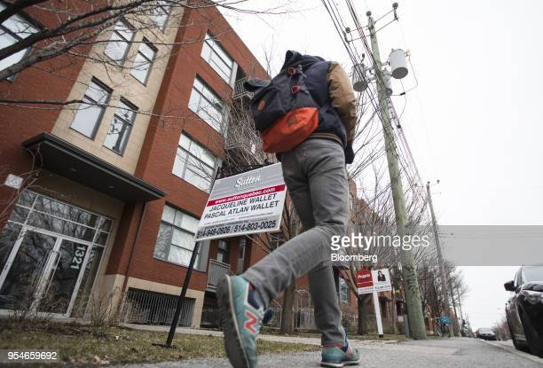 A pedestrian passes in front of a home for sale in the Le Plateau MontRoyal borough of Montreal Quebec Canada on Saturday April 14 2018 An economic...