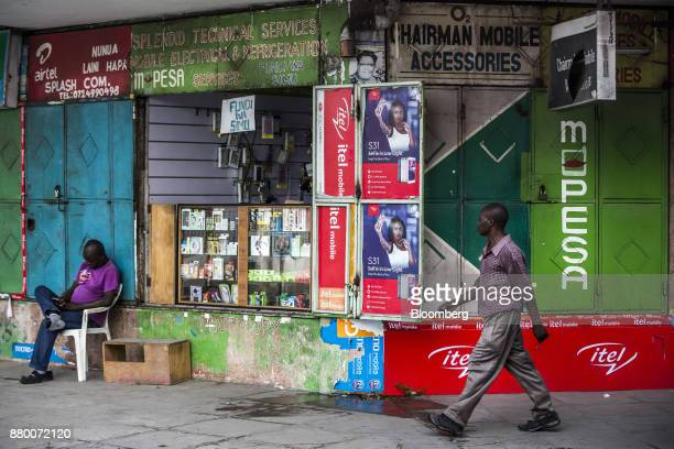 A pedestrian passes in front of a mobile phone accessories and MPesa banking service vendor in Mombasa Kenya on Thursday Nov 23 2017 The countrys...