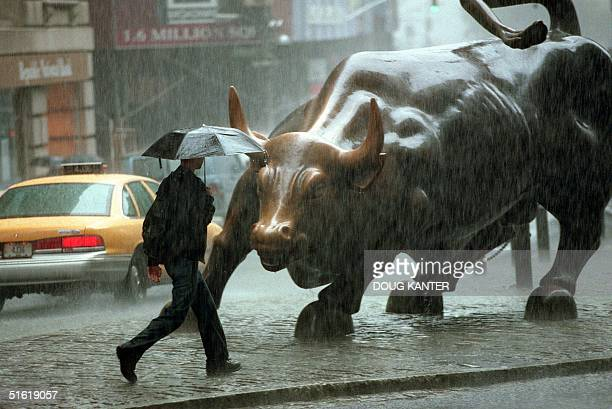 A pedestrian passes in front of a statue of a bull in the Wall Street area in New York City where rains from Hurricane Floyd hit 16 September 1999...