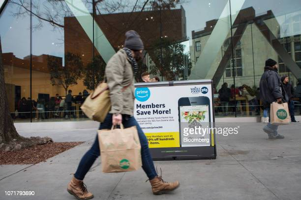A pedestrian passes in front of a Whole Foods Market Inc advertisement for Amazoncom Inc Prime members in the Brooklyn borough of New York US on...
