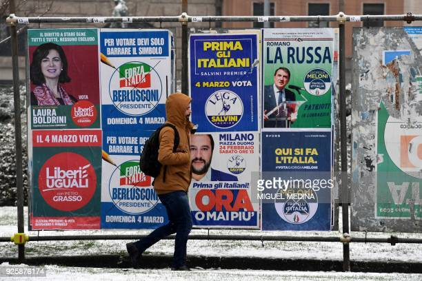 A pedestrian passes in front of election hoardings in Milan on March 1 prior to the Italian presidential elections Italian Prime Minister Paolo...