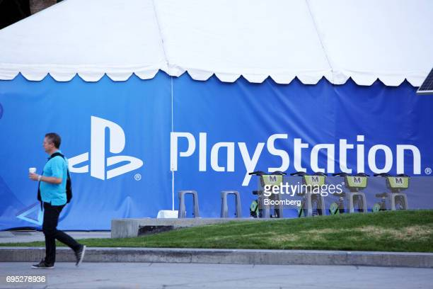 A pedestrian passes in front of Sony Corp PlayStation game console signage ahead of an Ubisoft Entertainment SA event in Los Angeles California US on...