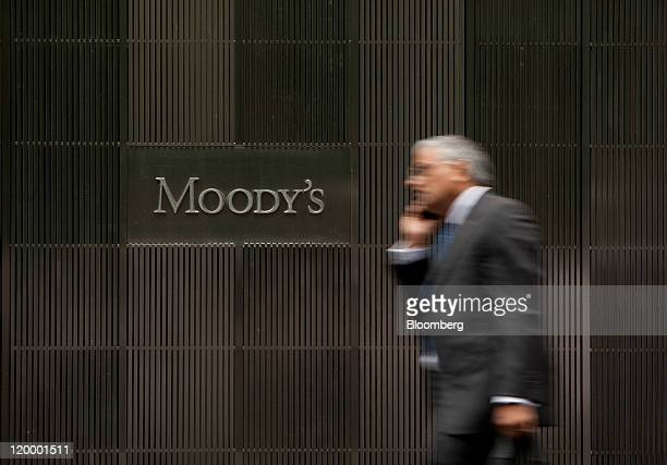A pedestrian passes in front of the Moody's Investors Service Inc headquarters in New York US on Thursday July 28 2011 Moody's Investors Service...