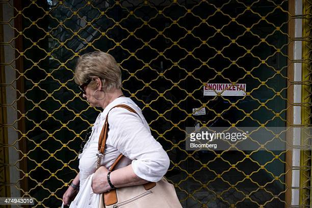 A pedestrian passes metal shutters outside the empty premises of a closed down retail store in central Thessaloniki Greece on Wednesday May 27 2015...