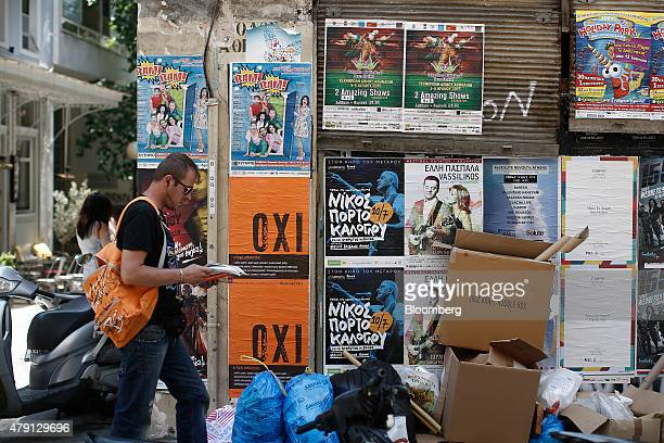 A pedestrian passes orange antiausterity posters with the word 'OXI' meaning 'NO' on a wall beside trash abandoned on a street in Athens Greece on...