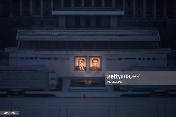TOPSHOT A pedestrian passes portraits of late North Korean leaders Kim IlSung and Kim JongIl in Pyongyang seen from the landmark Juche tower on...
