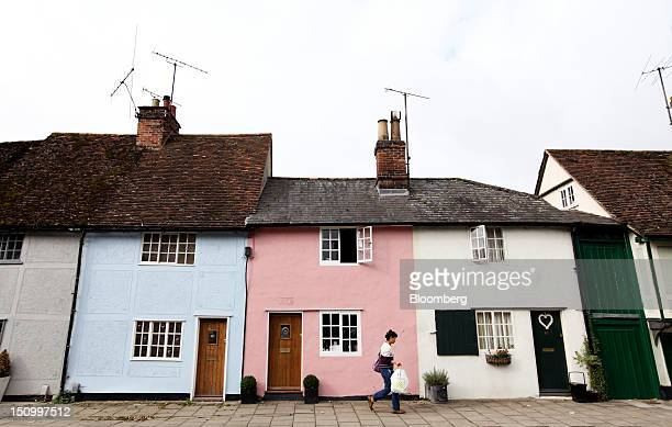 A pedestrian passes residential properties in Saffron Walden UK on Thursday Aug 30 2012 UK house prices fell in August for a second month as demand...