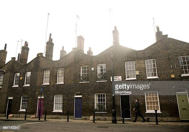 A pedestrian passes residential terraced properties in the Waterloo district of London UK on Monday Jan 20 2014 London houseprice growth slowed in...