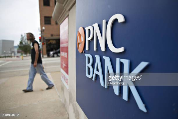 A pedestrian passes signage displayed at a PNC Financial Services Group Inc bank branch in Peoria Illinois US on Monday July 10 2017 PNC Financial...