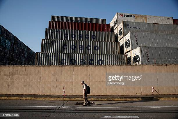 Pedestrian passes stacked COSCO Pacific Ltd. Branded shipping containers behind a perimeter wall in the commercial shipping area of Piraeus Port,...