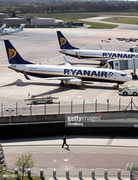 A pedestrian passes stationery Ryanair aircraft as they sit on the tarmac at Birmingham International airport in Birmingham UK on Tuesday April 20...