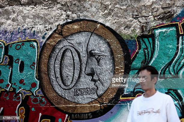A pedestrian passes street graffiti depicting a 'zero' euro coin on the wall of a parking lot in Athens Greece on Thursday June 4 2015 Greek Prime...