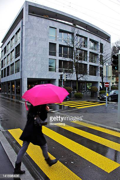 Pedestrian passes the building that houses the headquarters of Xstrata Plc in Zug, Switzerland, on Monday, March 19, 2012. Glencore International Plc...