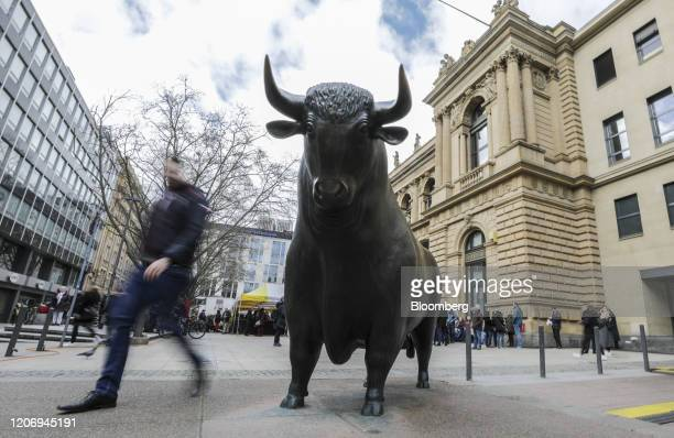Pedestrian passes the bull statue stands outside the Frankfurt Stock Exchange, operated by Deutsche Boerse AG, in Frankfurt, Germany, on Friday,...