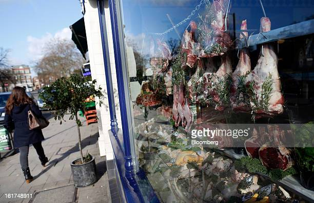 A pedestrian passes the dressed window display of a traditional butcher's shop in the Clapham district of London UK on Friday Feb 15 2013 While...