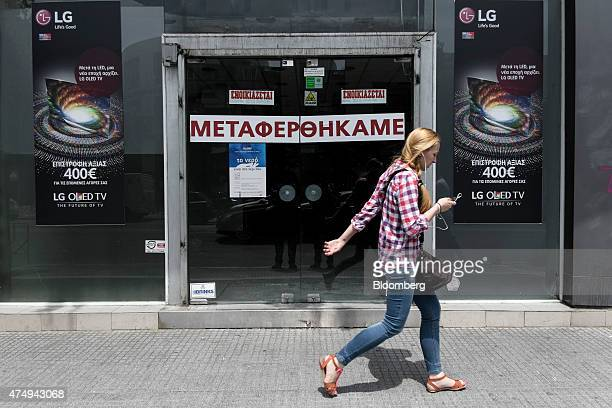 A pedestrian passes the entrance to a closed down electronics retail store in Thessaloniki Greece on Wednesday May 27 2015 Greek banks forced into a...