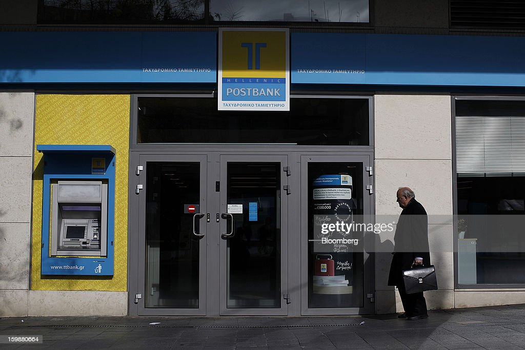 A pedestrian passes the entrance to a closed Hellenic Postbank SA bank branch in Athens, Greece, on Tuesday, Jan. 22, 2013. Euro-area finance ministers blessed the next disbursement of emergency aid for Greece, highlighting the goodwill that led to the unblocking of loans last month for Prime Minister Antonis Samaras's government. Photographer: Kostas Tsironis/Bloomberg via Getty Images