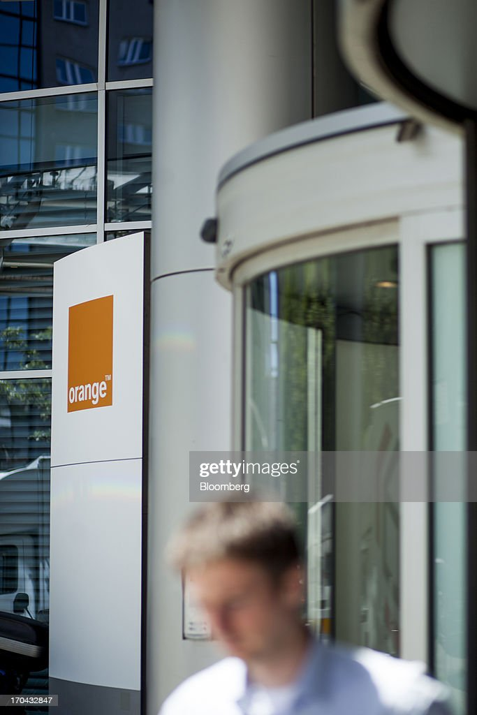 A pedestrian passes the entrance to the headquarters of Orange Polska, also known as Telekomunikacja Polska SA (TPSA), Poland's national telecommunications company, in Warsaw, Poland, on Wednesday, June 12, 2013. Cable providers are being drawn to Poland, the European Union's biggest eastern economy, because penetration levels are half that of neighboring Germany even as unemployment rises, according to a website presentation by the country's biggest TV network, Cyfrowy Polsat SA. Photographer: Bartek Sadowski/Bloomberg via Getty Images