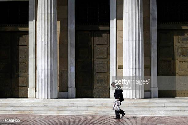 A pedestrian passes the entrance to the headquarters of the Bank of Greece in central Athens Greece on Thursday July 16 2015 While Greek lawmakers...
