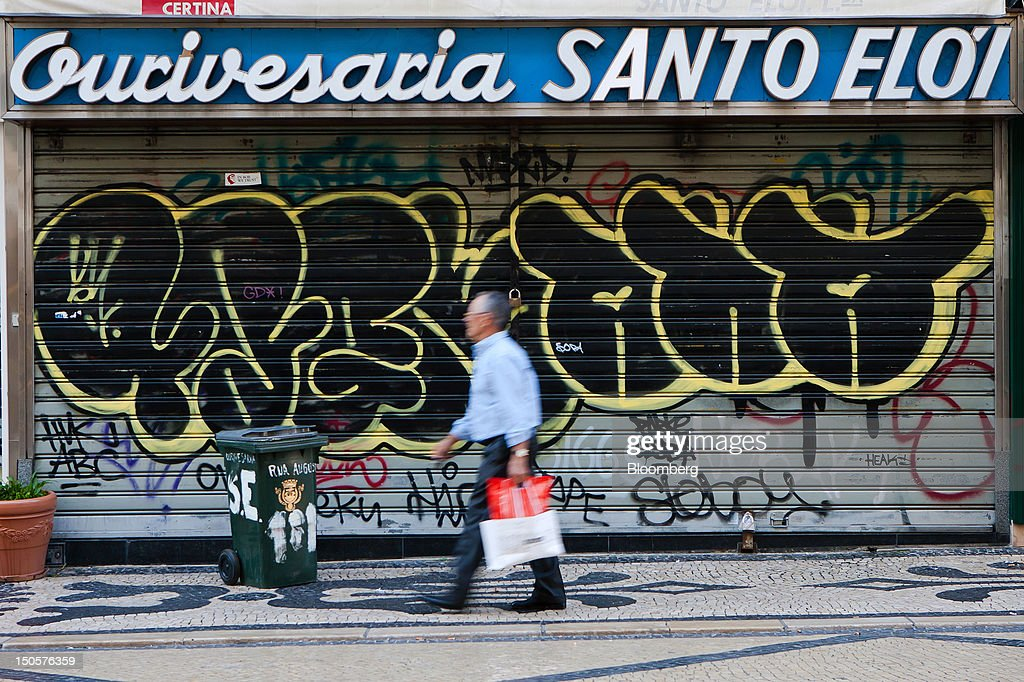 A pedestrian passes the graffiti-daubed shutters of a closed jewelry store in Lisbon, Portugal, on Wednesday, Aug. 22, 2012. In Portugal, the historical home of some of Europe's biggest gold reserves, the number of jewelry stores, which include cash-for-gold shops, increased 29 percent in 2011 from a year earlier, a study commissioned by parliament found. Photographer: Mario Proenca/Bloomberg via Getty Images