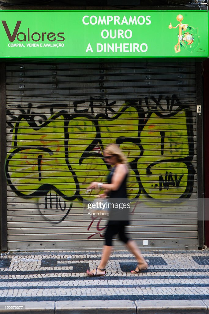 A pedestrian passes the graffiti-daubed shutters of a closed-down pawnbrokers store in Lisbon, Portugal, on Wednesday, Aug. 22, 2012. In Portugal, the historical home of some of Europe's biggest gold reserves, the number of jewelry stores, which include cash-for-gold shops, increased 29 percent in 2011 from a year earlier, a study commissioned by parliament found. Photographer: Mario Proenca/Bloomberg via Getty Images