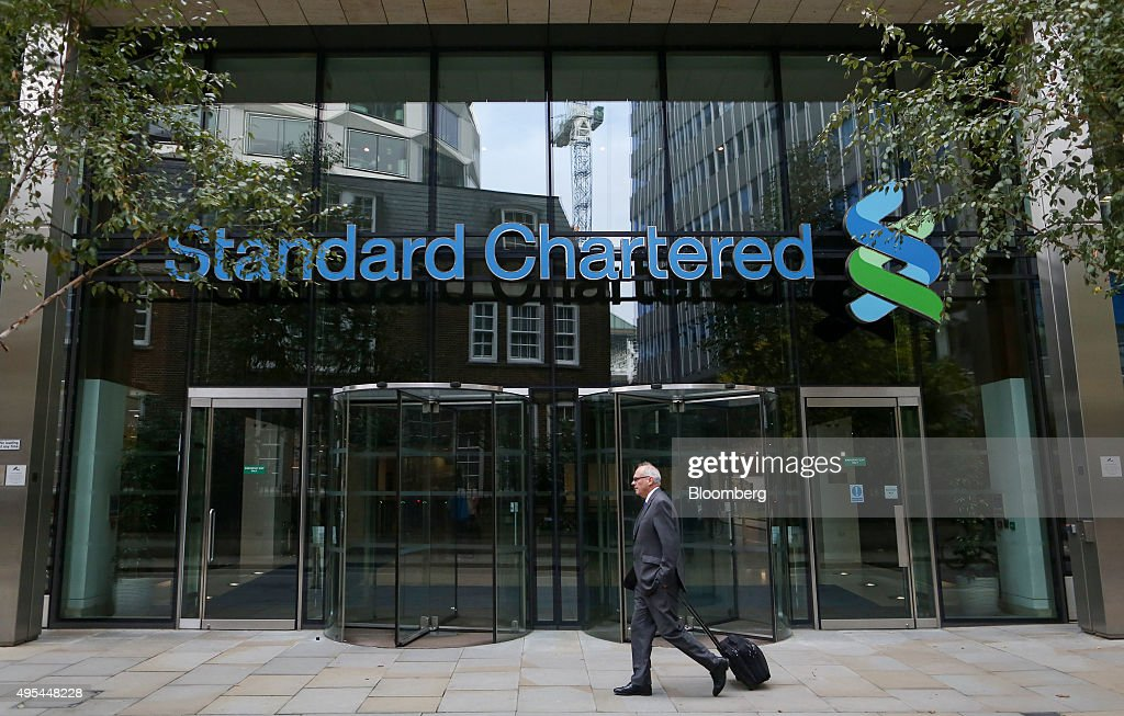A pedestrian passes the headquarters of Standard Chartered Plc in London, U.K. on Tuesday, Nov. 3, 2015. Standard Chartered Plc dropped the most in more than three years after the lender said it plans to eliminate 17 percent of its workforce, scrap the dividend and tap investors for $5.1 billion as Chief Executive Officer Bill Winters seeks to restore profit growth. Photographer: Chris Ratcliffe/Bloomberg via Getty Images