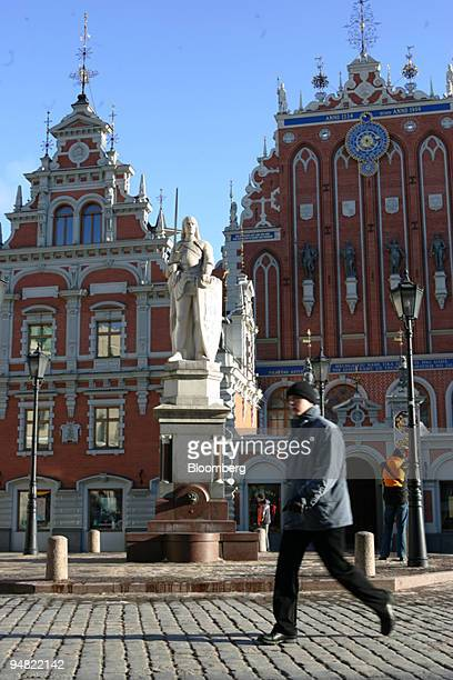 A pedestrian passes the Monument of Roland and Blackheads house in Riga Latvia Sunday March 20 2005