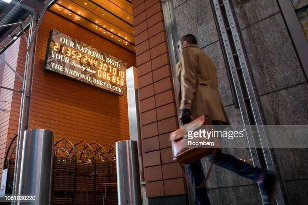 A pedestrian passes the National Debt Clock on West 43rd Street in New York US on Friday Jan 11 2019 US stocks dipped Friday as a decline in energy...