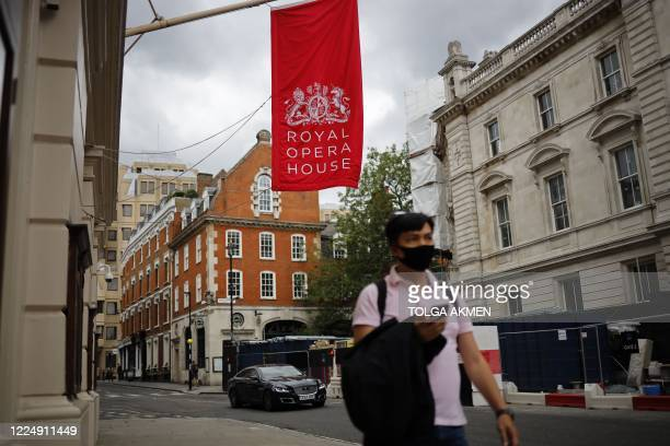Pedestrian passes the Royal Opera House, which remains closed due to restrictions to slow the spread of the novel coronavirusm, in London's West End...