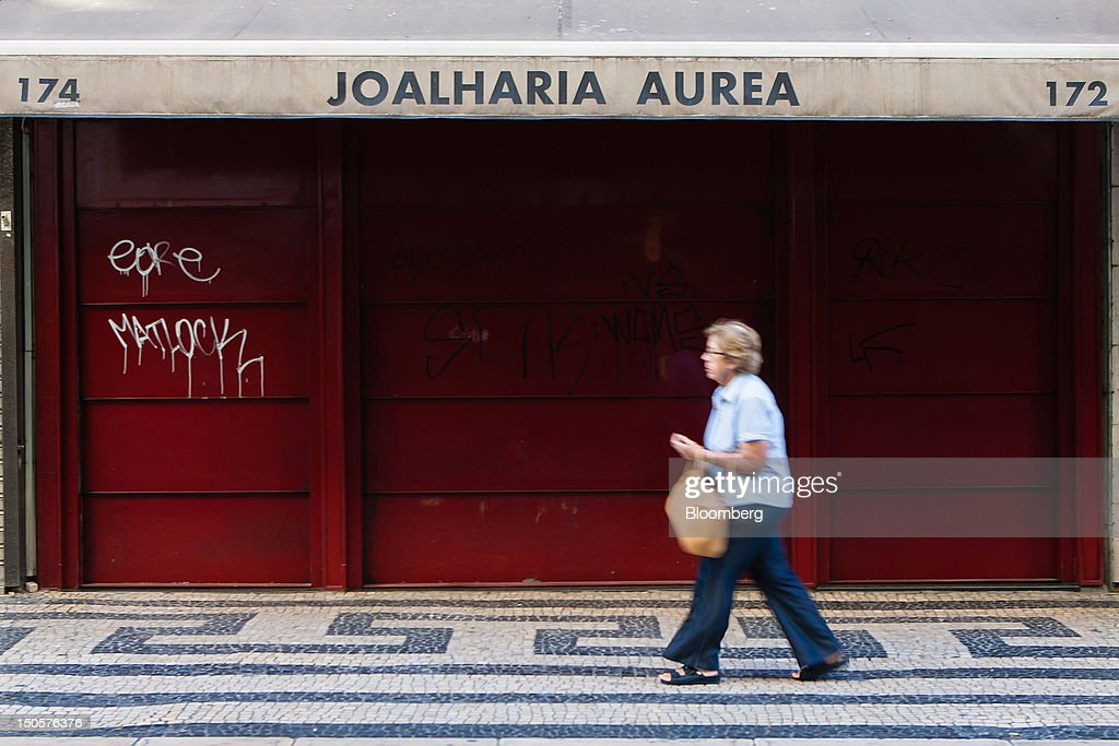 A pedestrian passes the shutters of a closed jewelry store in Lisbon, Portugal, on Wednesday, Aug. 22, 2012. In Portugal, the historical home of some of Europe's biggest gold reserves, the number of jewelry stores, which include cash-for-gold shops, increased 29 percent in 2011 from a year earlier, a study commissioned by parliament found. Photographer: Mario Proenca/Bloomberg via Getty Images