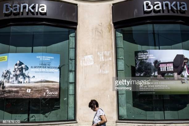 A pedestrian passes the windows of a Bankia SA bank branch in Barcelona Spain on Thursday Oct 5 2017 Catalan lenders such asCaixaBankSA andBanco...
