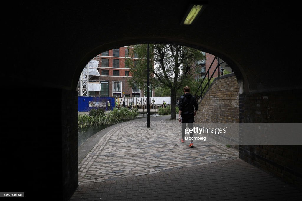 A pedestrian passes underneath a bridge in the Canada Water area of south London, U.K., on Wednesday, May 16, 2018. British Land Co. will seek approval to develop as many as 3,000 homes and work space equivalent to almost four Gherkin skyscrapers on a plot in south Londons Canada Water. Photographer: Chris Ratcliffe/Bloomberg via Getty Images