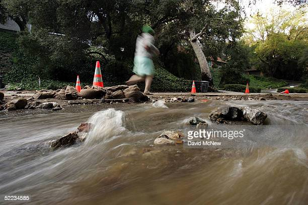 A pedestrian passes water and debris flowing down the road in Chevy Chase Canyon as southern California gets a break from the rains of the wettest...