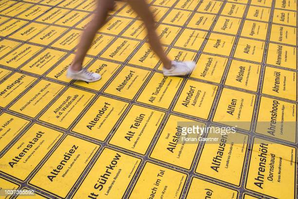 Pedestrian passing a square of about 11400 town signs of all municipalities in Germany on September 21 2018 in Berlin Germany On occasion of the...