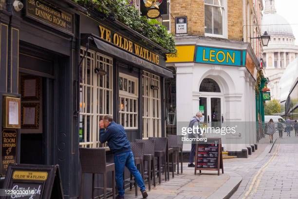 Pedestrian peers through the window of a public house in the City of London, U.K., on Monday, Oct. 12, 2020. The approach of Brexit has London...