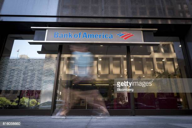 A pedestrian photographed with a slow shutter speed is seen passing in front of a Bank of America Corp branch in Chicago Illinois US on Saturday July...