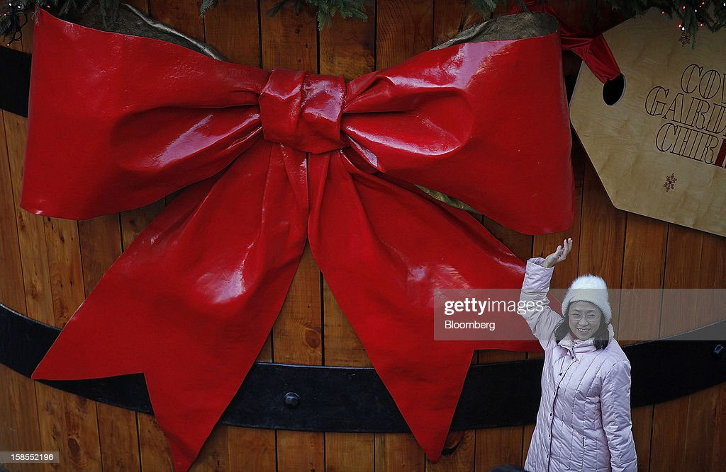 A pedestrian poses for a photograph next to a giant Christmas decoration in the Covent Garden shopping district of London, U.K., on Monday, Dec. 17, 2012. Retailers are relying on Christmas sales to help rescue a year when high unemployment and the debt crisis have blighted spending. Photographer: Simon Dawson/Bloomberg via Getty Images