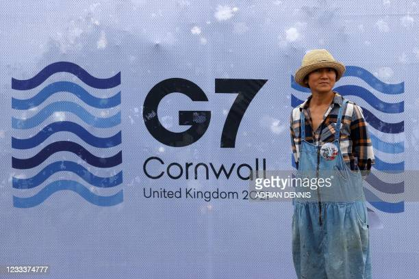 Pedestrian poses for a photograph with a G7 logo outside the media centre at Falmouth, Cornwall on June 10 ahead of the three-day G7 summit being...