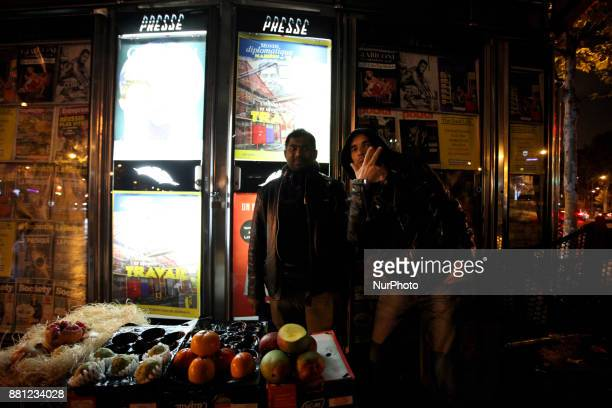 A pedestrian poses with a street vendor from Bangladesh in Paris France November 24 2017