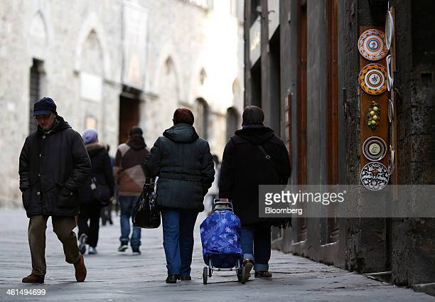 A pedestrian pulls a shopping trolley as she passes a porcelain store in Siena Italy on Wednesday Jan 8 2014 Banca Monte dei Paschi di Siena SpA the...