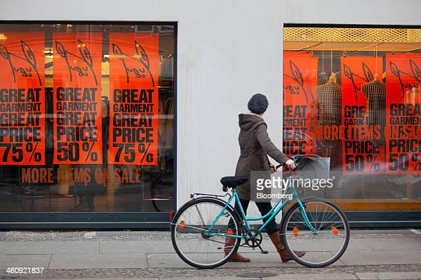 Pedestrian pushes a bicycle past a Weekday clothing fashion store, operated by Hennes & Mauritz AB, in Berlin, Germany, on Saturday, Jan. 4, 2014....