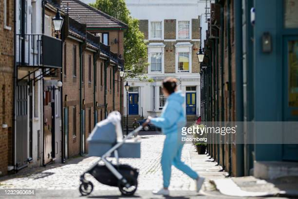 Pedestrian pushes a pram past a cobbled street in the Notting Hill district of London, U.K., on Wednesday, May 12, 2021. An extreme example of...