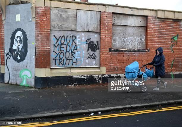 Pedestrian pushes a pram past graffiti in Hull, in north-east England on November 30, 2020. - Hull will return to the England's highest coronavirus...