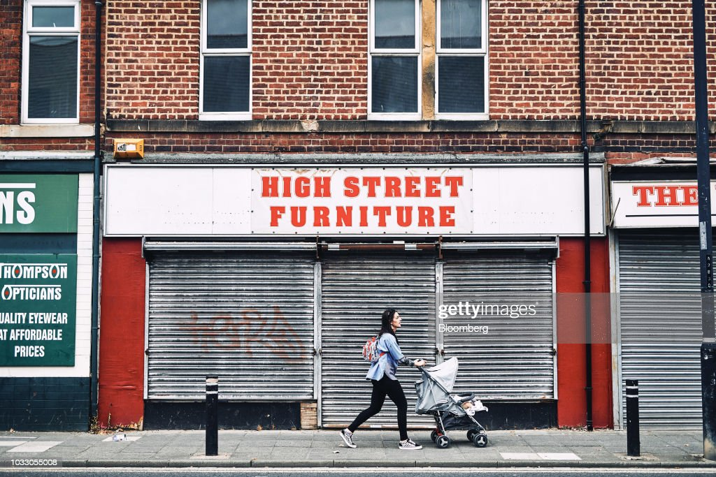 A pedestrian pushes a stroller passed a shuttered furniture retail shop in Wallsend, U.K., on Thursday, Sept. 6, 2018. The northeast of England illustrates the precarious position facing many parts of the U.K. just six months before the country is due to leave the EU. Photographer: Matthew Lloyd/Bloomberg via Getty Images