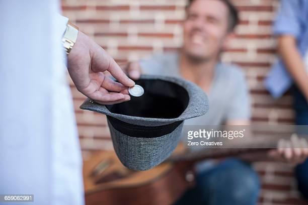 Pedestrian putting money in street musicians hat, mid section