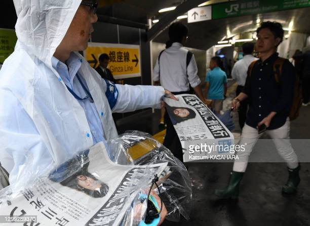 Pedestrian receives an extra news paper which reports the execution of Aum Shinrikyo leader Shoko Asahara and other six follwers at Shinbashi...