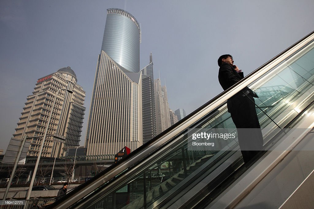 A pedestrian rides an escalator while talking on a mobile phone past commercial buildings in the Pudong area of Shanghai, China, on Wednesday, Jan. 30, 2013. China's economic growth accelerated for the first time in two years as government efforts to revive demand drove a rebound in industrial output, retail sales and the housing market.Photographer: Tomohiro Ohsumi/Bloomberg via Getty Images