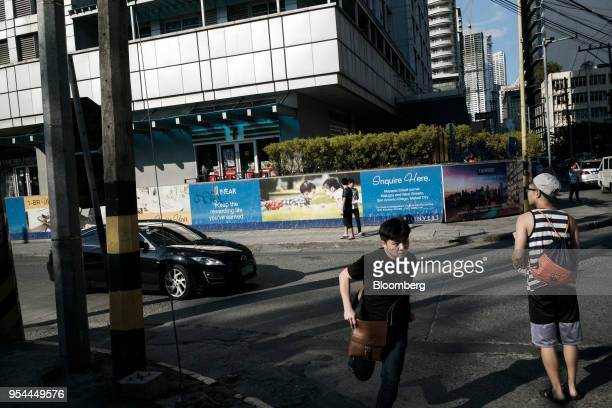 A pedestrian runs across a road in front of The Linear Makati development in the San Antonio Village area of Makati City Manila the Philippines on...